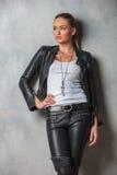 Junge Frau in der Lederjacke schaut, um mit Seiten zu versehen Lizenzfreie Stockfotos