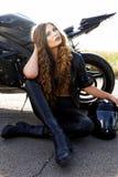 Junge Frau in der ledernen Kleidung nahe einem Motorrad lizenzfreie stockfotos