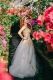 Junge Frau in der luxuriösen Kleiderstellung in geblühtem Garten lizenzfreie stockfotos
