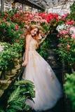 Junge Frau in der luxuriösen Kleiderstellung in geblühtem Garten lizenzfreies stockfoto