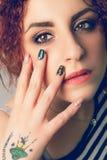 Junge Frau der Make-upgesichts- und -handnägel Konformistentätowierung Stockfoto