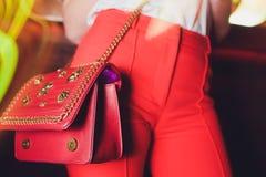 Junge Frau der Mode in den roten Jeans und in der Strickjacke mit roter Taschenkupplung in den Händen nahe Straßenwandnahaufnahme lizenzfreie stockfotografie