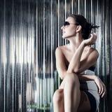 Junge Frau der Mode, die auf Stuhl sitzt Lizenzfreies Stockbild