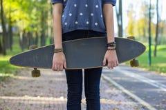 Junge Frau der Mode, die mit einem longboard aufwirft Stockfoto