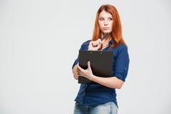 Junge Frau der nachdenklichen schönen Rothaarigen, die Klemmbrett und das Denken hält Lizenzfreie Stockfotografie