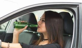 Junge Frau der Nahaufnahme, die im Auto hält grüne Bierflasche und trinkt sitzt, wie vom äußeren Treiberfenster gesehen, weiblich lizenzfreie stockfotos