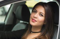 Junge Frau der Nahaufnahme, die im Auto lächelt zur Kamera sitzt, wie vom äußeren Treiberfenster gesehen, weibliches Fahrerkonzep lizenzfreie stockbilder