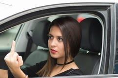 Junge Frau der Nahaufnahme, die im Auto verärgert gibt den Finger sitzt, wie vom äußeren Treiberfenster gesehen, weibliches Fahre Lizenzfreie Stockfotos