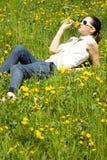 Junge Frau in der Natur, die eine Blume riecht Stockbild