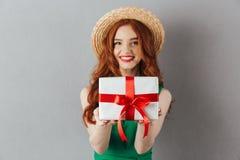 Junge Frau der netten Rothaarigen im grünen Kleid, das Geschenk hält stockfoto