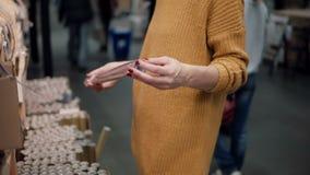 Junge Frau in der orange Strickjacke wählt Packpapier Weihnachtsdekor Lizenzfreie Stockfotos