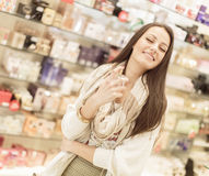 Junge Frau in der Parfümerie stockbilder