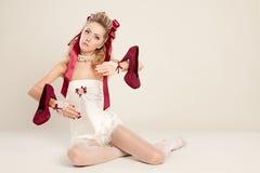 Junge Frau in der Puppenart mit rotem Bogen und rotem hochhackigem Lizenzfreie Stockfotos