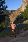Junge Frau in der rosa Spitze, die oben steilen Hang mit Gebirgsaussicht laufen lässt lizenzfreies stockbild