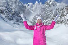 Junge Frau in der rosa Winterjacke, in den Handschuhen und in werfendem Schnee des warmen Hutes in der Luft, lächelnd, Berg hinte stockbilder
