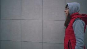 Junge Frau in der roten ärmellosen Jacke geht nahe bei grauer Wand des Gebäudes stock footage