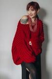 Junge Frau in der roten übergroßen Strickjacke und im schwarzen Rock Lizenzfreie Stockfotografie