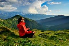 Junge Frau in der roten Jacke, die in der Yogahaltung in den Bergen sitzt Stockfoto