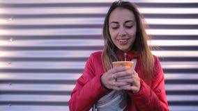 Junge Frau in der roten Jacke mit trinkendem Kaffee der Blue Jeans Taillen-Tasche draußen auf einem Metallwandhintergrund stock video