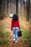 Junge Frau in der roten Lederjacke gehend in Wald stockfotografie