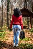 Junge Frau in der roten Lederjacke gehend in Wald stockbild