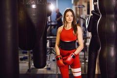 Junge Frau in der roten Sportkleidung und in den Boxhandschuhen, Züge mit einer boxenden Birne in einer dunklen Turnhalle stockfotografie