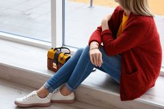 Junge Frau in der roten Wolljacke nahe Fenster stockfotos