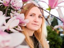 Junge Frau der Schönheit, die im Frühjahr Magnoliengarten der Natur genießt Romantisches Mode-Modell im Blütenblumenporträt lizenzfreies stockfoto