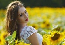 Junge Frau der Schönheit im Sonnenblumenfeld Lizenzfreie Stockfotos