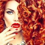 Junge Frau der Schönheit mit dem gelockten roten Haar Stockbild