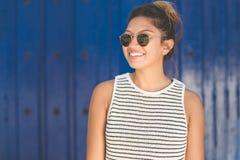 Junge Frau in der Sonnenbrille auf dem blauen Hintergrundlächeln Stockfotografie