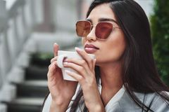 Junge Frau in der Sonnenbrille, die bei Tisch im Café hält Schale s sitzt lizenzfreie stockbilder