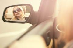 Junge Frau in der Sonnenbrille, die im Autorückspiegel schaut Stockbilder