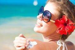 Junge Frau in der Sonnenbrille, die an Sonnencreme setzt Lizenzfreies Stockbild