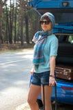 Junge Frau in der Sonnenbrille nahe dem Auto mit einem Koffer Stockfotografie