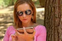 Junge Frau in der Sonnenbrille, sitzend auf einer Bank im Park, Arbeitsw lizenzfreie stockbilder
