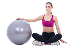 Junge Frau in der Sportkleidung, die mit dem Eignungsball an lokalisiert sitzt Stockbild