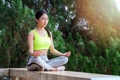 Junge Frau in der Sportkleidung meditierend Lizenzfreie Stockfotos