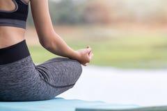 Junge Frau in der Sportkleidung meditierend beim Sitzen in der Lotoshaltung Lizenzfreies Stockbild