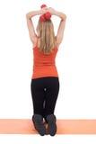 Junge Frau in der Sportkleidung zurück ausbildend mit den roten Dummköpfen lizenzfreie stockbilder