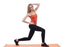 Junge Frau in der Sportkleidung zurück ausbildend und in den Beinen auf einer Matte lizenzfreie stockfotografie