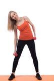 Junge Frau in der Sportkleidung zurück ausbildend und Seite mit Dummköpfen stockbilder
