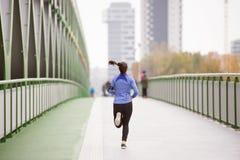 Junge Frau in der Stadt, die auf grüner Stahlbrücke läuft Lizenzfreies Stockfoto