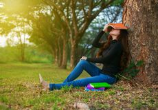 Junge Frau in der Stresssituation, wenn ein Buch im Park gelesen wird lizenzfreies stockfoto