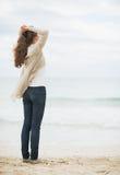 Junge Frau in der Strickjacke, die auf einsamem Strand sich entspannt Lizenzfreie Stockfotografie