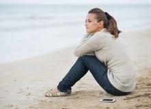 Junge Frau in der Strickjacke mit dem Handy, der auf einsamem Strand sitzt Lizenzfreie Stockbilder