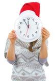 Junge Frau in der Strickjacke und in Weihnachtshut, die hinter Uhr sich verstecken Lizenzfreie Stockfotos