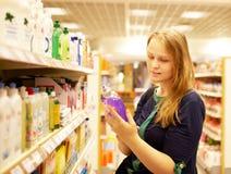 Junge Frau in der Supermarktlesebeschreibung Stockfotografie