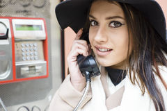 Junge Frau an der Telefonzelle Stockfotos