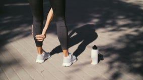 Junge Frau der Trainingseignungsverletzungen mit den Schmerz im Bein mischt während der Übung draußen mit stock video footage
